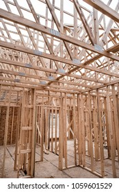 Interior of new home construction work site showing skeletal structure of walls and roof trusses constructed of wood 2x4's, waferboard and plywood flooring and walls