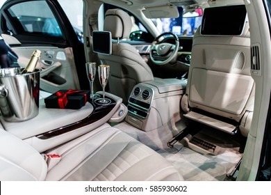 Interior of new luxury car prepared for valentine's day romantic dinner. Champagne and gift waiting in wood and white leather interior.