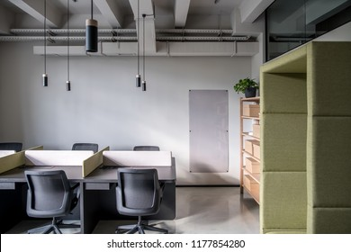 Interior in an office in a loft style with gray walls. There are black tables with partitions, chairs, wooden shelves with boxes and a plant, green fancy armchair, board, hanging lamps. Horizontal.