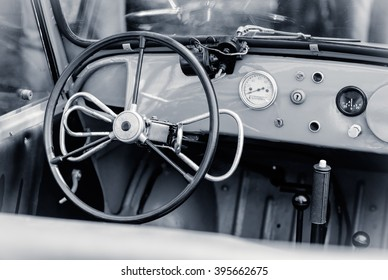 Interior of the old automobile with steering wheel and dashboard. Retro car in vintage style. Old car with manual control for persons with disabilities.
