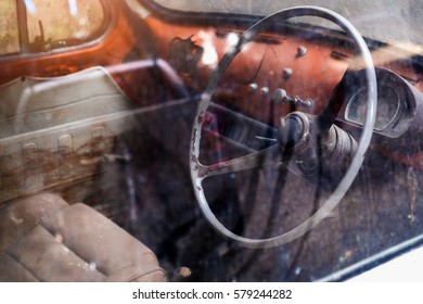Interior of the old car and steering wheel with reflection of the dirty window