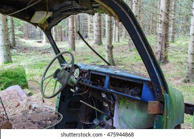 Interior of an old car wreck standing in woods