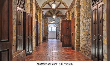 the interior of an old stone manor. many wooden doors