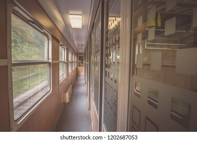 Interior of an older train coach with compartments. Aisle of a train wagon with compartments.