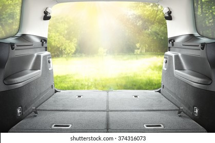 interior of open car trunk with green landscape