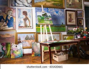 Interior of a painters studio or gallery with colorful canvases covering a variety of subjects hanging on the wall and an unfinished painting on a wooden easel