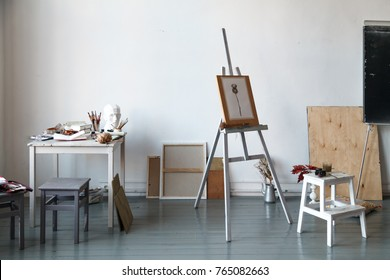 Interior of painting studio of freelance artist. Gypsum head, brushes, pencills, ink and paint bottles with sketchbooks on the table. Freelance artist lifestyle concept