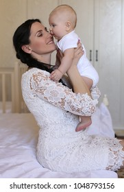 interior photo of beautiful mother with dark hair in elegant clothes playing with her little son