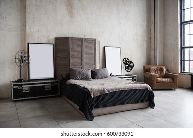 Interior photo of modern loft bedroom with high ceiling, cement walls, concrete floor, window, design accessories, leather armchair and poster mock up.