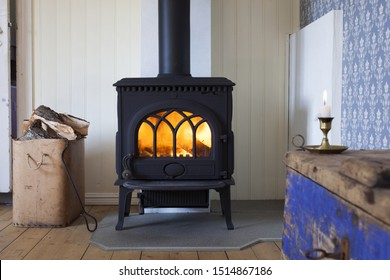 Interior photo with wood burning in metal stove, box of firewood and part of old weathered blue chest in corner. Focus on stove.