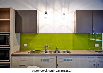 Interior photography of a contemporary design corporate office break out area, a kitchen washing up area with sink, pendant lighting and microwave ovens