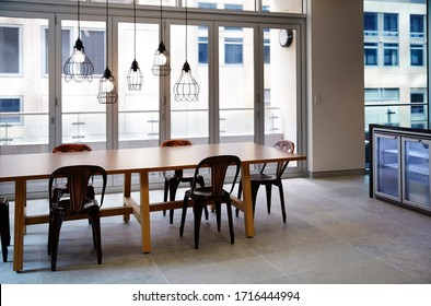 Interior photography of a contemporary design corporate office break out area with kitchen and lunch table and chairs with concrete finish tiles and industrial style pendant lighting