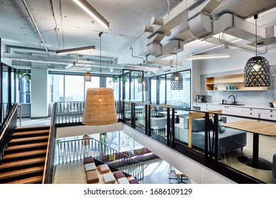 Interior photography of a contemporary designer corporate office breakout area with kitchen, booths, pendant lighting and polished concrete floors
