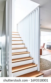 Interior photography of a contemporary home with a timber and white staircase with a lounge room and timber deck patio in the background