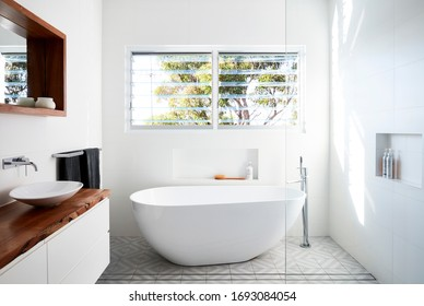 Interior photography of a contemporary white bathroom with freestanding tub, louvred windows, wall hung timber vanity unit and grey Moroccan tiles