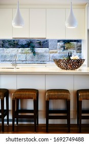 Interior photography of contemporary white kitchen with a breakfast bar with brown timber and rattan stools, a glass splash back, timber floors and pendant lighting