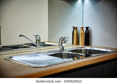Interior photography of corner of kitchen wash up area with mirror splash back and cleaning products