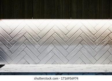 Interior photography detail of a splash back in a kitchen with a marbel bench top, herringbone mosaic tiles and strip lighting under the cabinetry