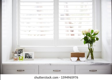 Interior photography detail of a white bedroom with window and plantation shutters, decorative objects, roses and picture frames on a marble topped chest of drawers