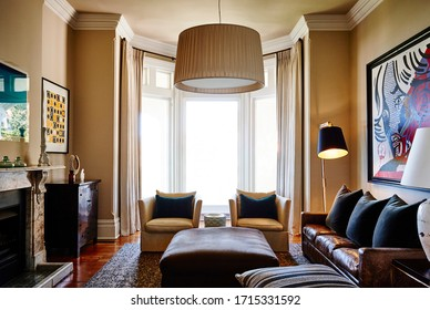 Interior photography of an eclectic stylish lounge room in a Victorian mansion with a leather couch, velvet armchairs, artwork and decorative objects
