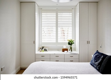 Interior photography of fresh and light bedroom with white bed, coastal style cushions, white built in cupboards and plantation shutters with decorative objects