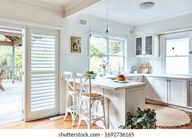 Interior photography of a fresh white Hamptons style kitchen with breakfast bar, cross back bar stools, polished floor boards and a door way opening up to a back deck