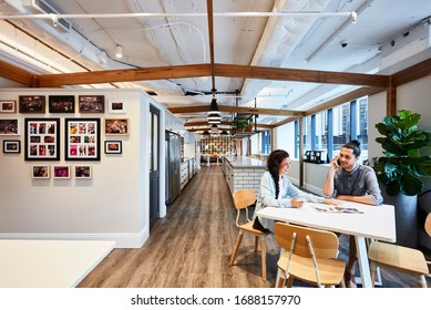 Interior photography of a large contemporary design corporate office break out area, staff holding a meeting at a lunch table with a kitchen in the background