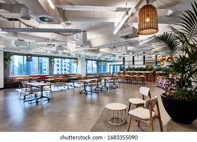 Interior photography of a large office breakout area in a city building with kitchen, tables and chairs, pendant lighting, exposed concrete ceilings, concrete flooring and city views