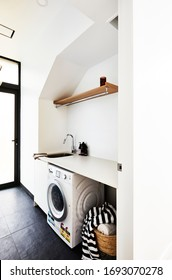 Interior photography of a light fresh laundry room with a washing machine, sink, timber shelf with clothing rail and a laundry basket with towels