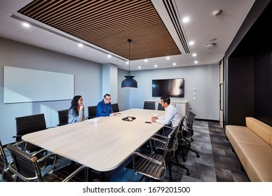 Interior photography of a modern corporate board room with a wall mounted screen, beech storage cabinet, meeting table and door, black leather chairs, timber ceiling detail and staff holding a meeting