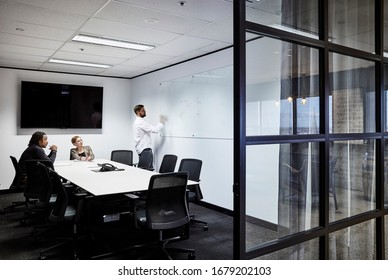 Interior photography of a modern corporate board room with a large meeting table, black chairs and staff members holding a meeting, shot through a glass entrance doorway