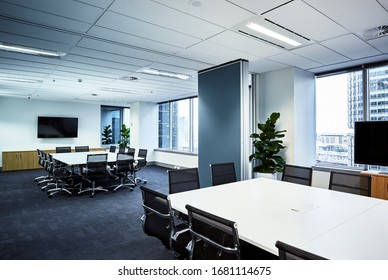 Interior photography of a modern corporate board room with a concertina wall leading to another board room, city views from windows