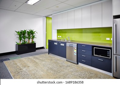Interior photography of a modern corporate office break out area, an office kitchen with grey and white cabinetry, a green splash back and polished concrete floors