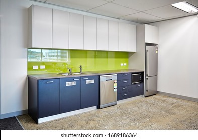 Interior photography of a modern corporate office break out area, an office kitchen with grey and white cabinetry, a green splash back and a polished concrete floor