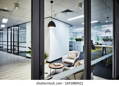 Interior photography of a modern corporate office reception waiting area with cream arm chairs, pot plants and pendant lighting with an open plan office in the background, shot through glass entrance