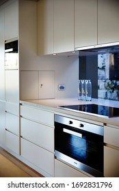 Interior photography of a modern kitchen with white cabinetry, a stainless steel oven, induction stove and glass splash back looking into a courtyard