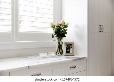 Interior photography of a modern light bedroom corner with built in cupboards, lowline drawers with marble bench top, vase of roses, trinket bowls and a picture frame