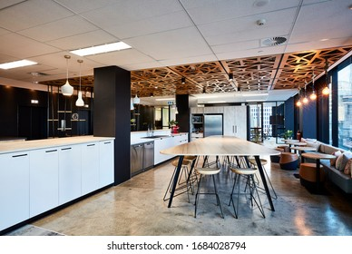 Interior photography of a modern office breakout area with a kitchen, timber lunch table, laser cut wooden ceiling, polished concrete floors, banquette seating, tables and stools with a city view