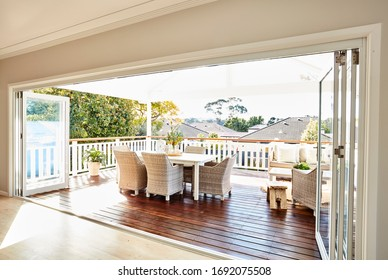 Interior photography of a residential timber deck in a coastal style home with cane furniture table setting