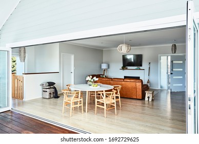 Interior photography of a Scandinavian style dining table setting with wishbone chairs looking through to a lounge room with a tan leather sofa and wall mounted tv and front door to the house