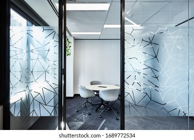 Interior photography of a simple meeting room with a round table, white chairs shot through the glass walls and doorway from a hallway