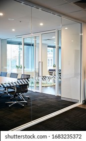 Interior photography of a simple modern corporate board room shot from outside with neutral tones with a timber meeting table, black chairs and glass walls with a reception area in the background