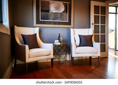 Interior photography of a sitting room with two cream arm chairs with cushions, a side table with a wine bottle and glasses, framed art and French doors with a polished timber floor