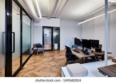 Interior photography of a small stylish modern corporate office with desks and a parquetry floor