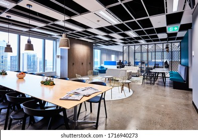 Interior photography of a stylish corporate breakout area with long lunch table and chairs, meeting areas and lounge with city views, an open plan office in the background