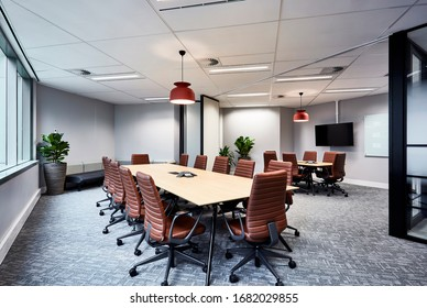 Interior photography of two modern board rooms divided by a concertina wall with pendant lighting, long timber meeting tables, tan leather chairs, pot plants and wall mounted screens