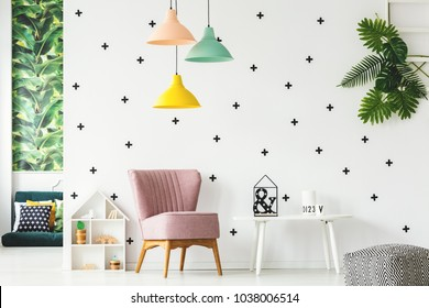 Interior of playroom with pink armchair, colorful chandeliers and wall decorated with stickers