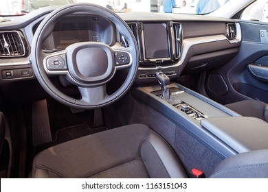 Interior of popular mass modern car. Comfortable gray textile seats. Car inside driver place. Front seats with steering wheel & dashboard.