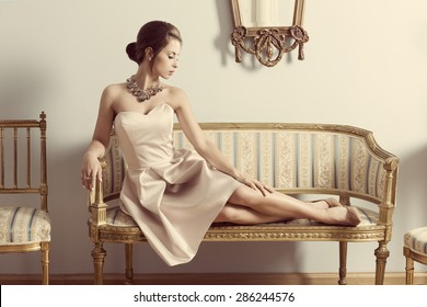interior portrait of brunette elegant girl lying on retro sofa in aristocratic room. Wearing pink dress, precious jewellery and classic hair-style. Luxury atmosphere