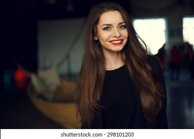 Interior portrait of young beautiful pretty smiling woman with long brown hair. Upper body shot